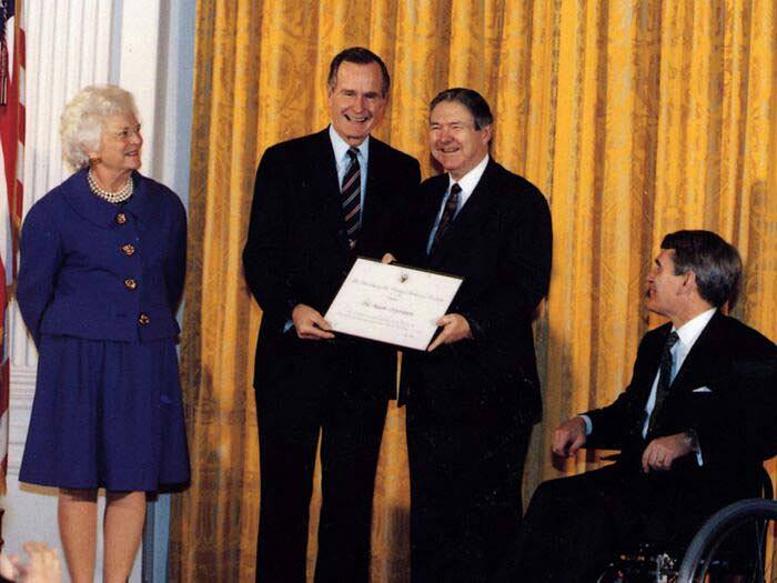 President George H.W. Bush presents Frank Bennack with a certificate for Hearst's support of initiatives to hire people with disabilities while First Lady Barbara Bush looks on, circa 1990