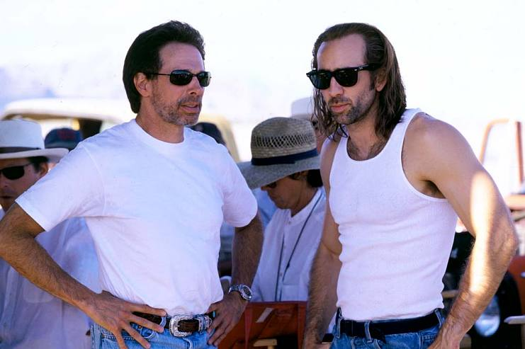 Jerry Bruckheimer talks to Nicolas Cage on the set of Con Air, 1996