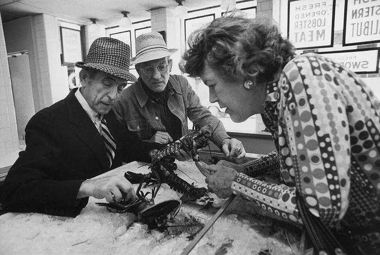 Julia and Paul Child (center) examining lobsters at a Boston market in 1975 with characteristic care
