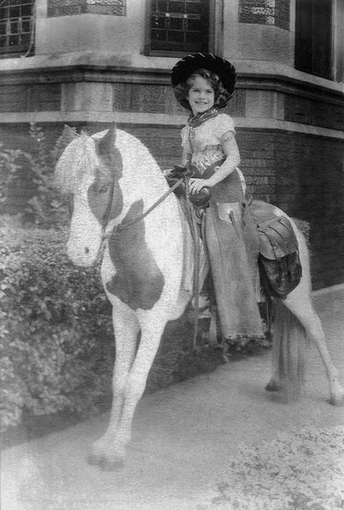 Sherry Lansing as a child on a hobbyhorse in front of her grandmother's home, Chicago, 1950s
