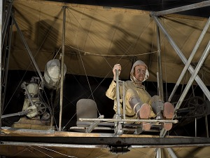 Pilot model in seat of 1909 Wright Military Flyer aircraft next to motor-thumbnail 58