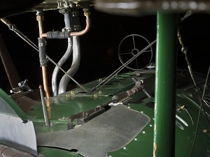 Pipes and metal pieces on dashboard of cockpit of green and brown Spad XIII