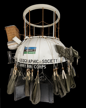 Ball-shaped metal balloon cabin with many canvas ballast bags hanging around center-thumbnail 1