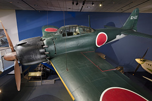Side of green tri-blade propellered Zero Fighter aircraft hanging in museum-thumbnail 16