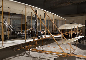 Front of 1903 Wright Flyer with model of Wright Brother laying flat in aricraft-thumbnail 3
