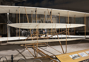 Front of 1903 Wright Flyer with model of Wright Brother laying flat in aricraft-thumbnail 4
