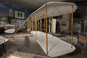 Side of wood, fabric, and metal canard biplane 1903 Wright Flyer in museum