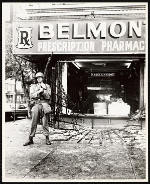 Image for Photograph of a solider guarding a looted store in the Newark Riots
