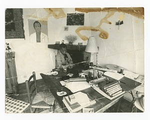 Photograph of James Baldwin seated at his work table