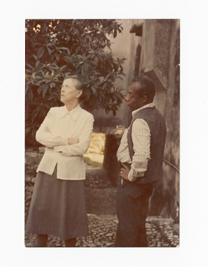 Photograph of James Baldwin standing with the owner of his French home