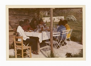 Photograph of James Baldwin and friends sitting outside around a table