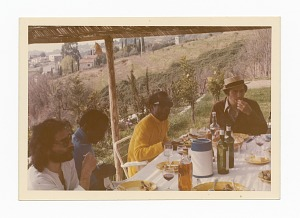 Photograph of James Baldwin and three friends sitting outside around a table