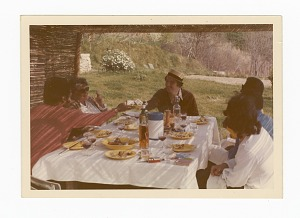 Photograph of James Baldwin and five friends sitting outside around a table