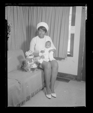 Image for Studio Portrait of a Mother Sitting on a Sofa Holding her Infant on her Lap