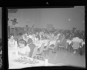 Image for Indoor Photo of Men and Women Sitting at Tables, Thelma Barnes