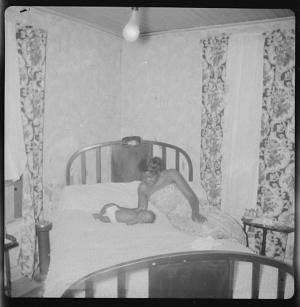 Image for Indoor Photo of a Mother Sitting on a Bed Looking at her Infant