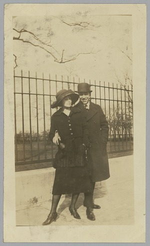 Image for Photo of man standing with his arm around woman in front of fence