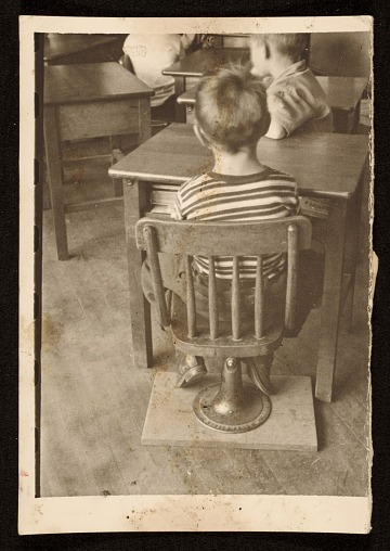 thumbnail image for Source material for <em>Tribute to the American Working People</em>. A boy seated in a chair
