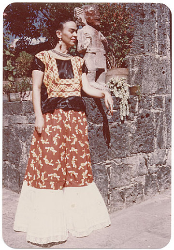 thumbnail image for Frida Kahlo standing by a stone wall