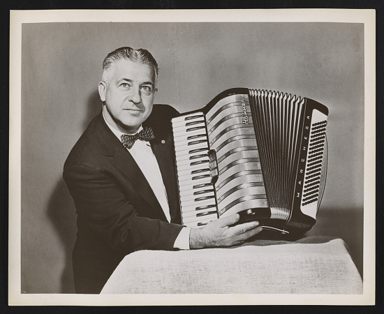 image for Photograph of John Vassos holding the Marchesa model accordion he designed for M. Hohner