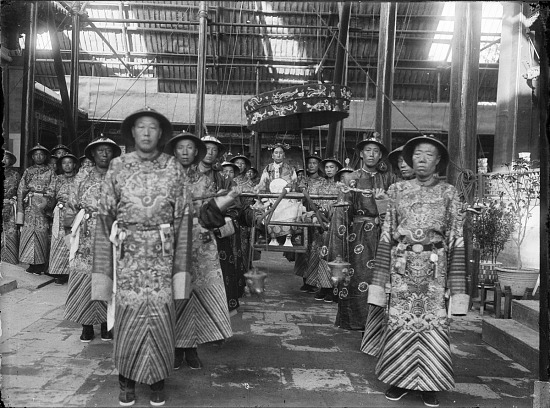 image for The Empress Dowager Cixi in sedan chair surrounded by eunuchs in front of Renshoudian, Summer Palace, Beijing 1903-1905