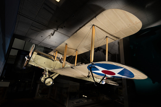 Tan De Havilland DH-4 biplane hanging in museum