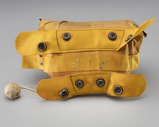 Straps on back of yellow rubber life vest with ball of cork attached by string