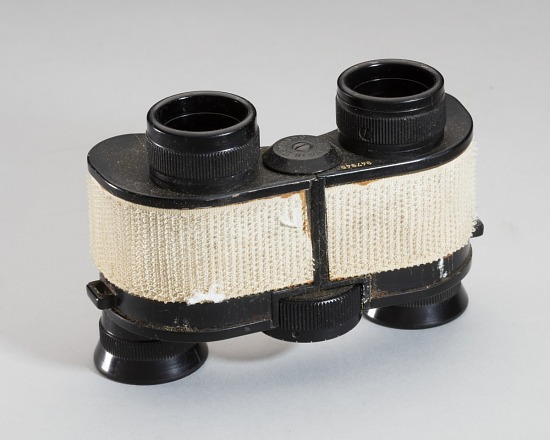 Top of small black binoculars with cream-colored Velcro patches attached to exterior