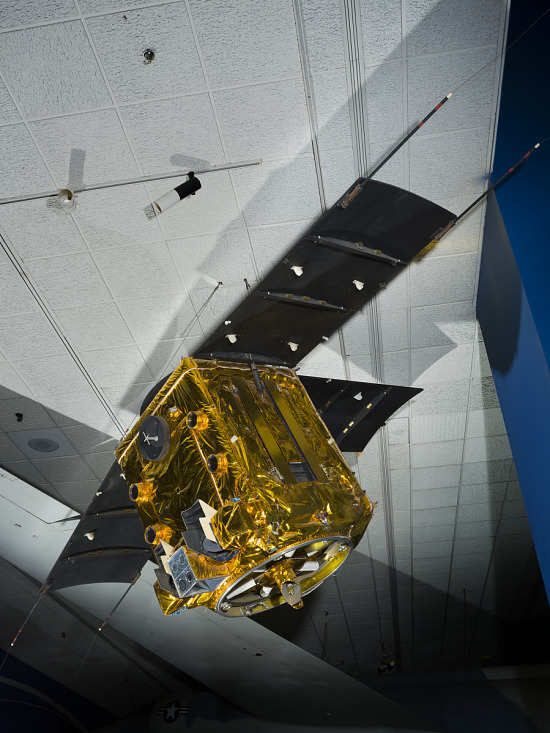 Gold-covered cube shaped sattelite with solar array paddles attached to three sides hanging in                 museum