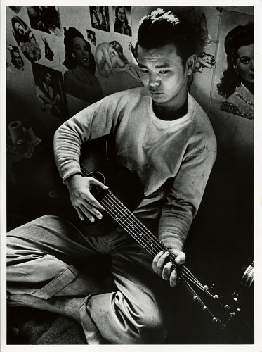 image for Young Japanese man strumming a guitar inside the Tule Lake Segregation Center