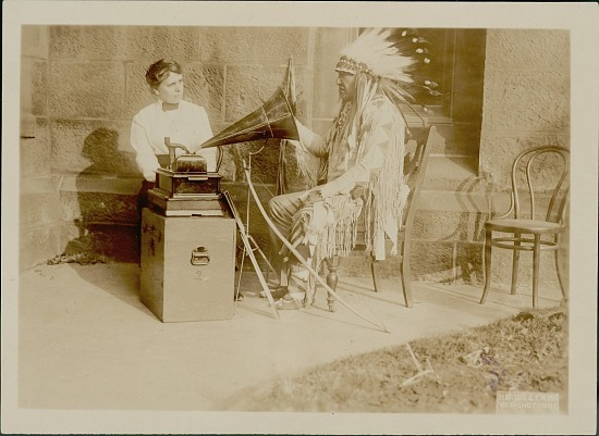 image for Mountain Chief, Chief of Montana Blackfeet, in Native Dress With Bow, Arrows, and Lance, Listening to Song Being Played On Phonograph and Interpreting It in Sign Language to Frances Densmore, Ethnologist MAR 1916