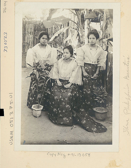 image for Three Young Women in Costume Near Banana Trees and Woven Bamboo Fence 1904