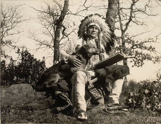 image for Acee Blue Eagle Wearing Feathered Headdress and Buckskin Clothing, Holding Book and Sitting Near Dog n.d. Photo Reproduction
