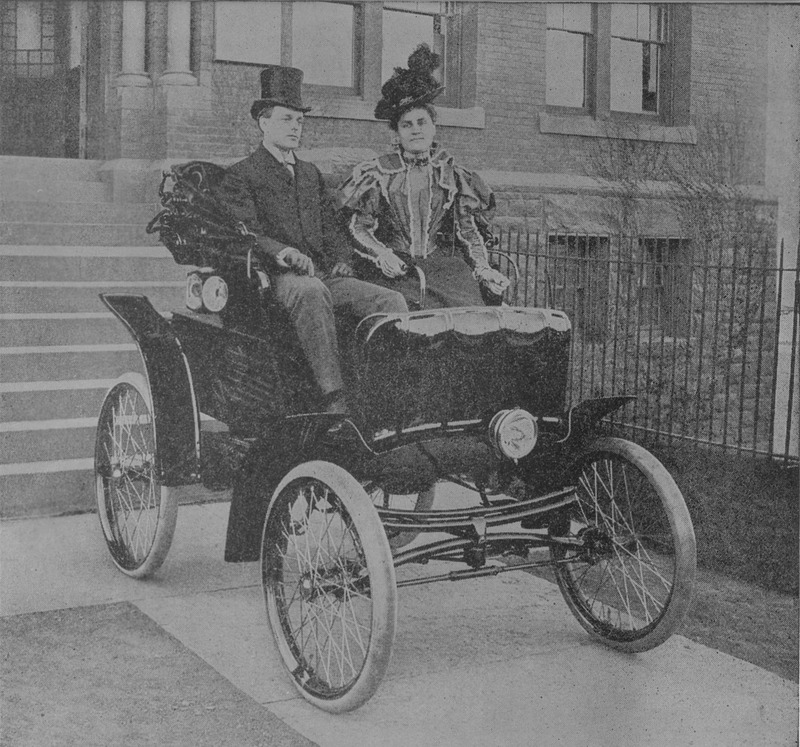 A man and a woman ride in a Columbia electric car, the woman rests her hand on the steering tiller.