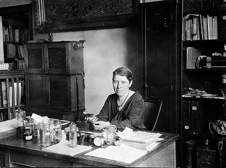 Doris M. Cochran at Desk Holding Frog