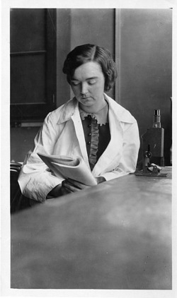 Mary Van Rensselaer Buell (1893-1969), sitting in lab with microscope, reading paper