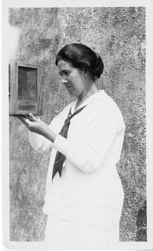 Estrella Eleanor Carothers (1883-1957), standing outside holding specimen case