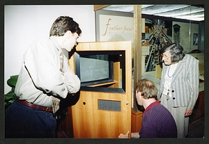 """Roxie Laybourne looking on as a man opens the television cabinet in the """"Feather Focus"""" Exhibit"""
